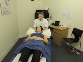 Physiotherapist performing head and neck massage.